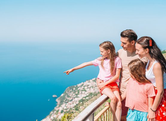 Summer holiday in Italy. Young family of four on the background, Amalfi Coast, Italy