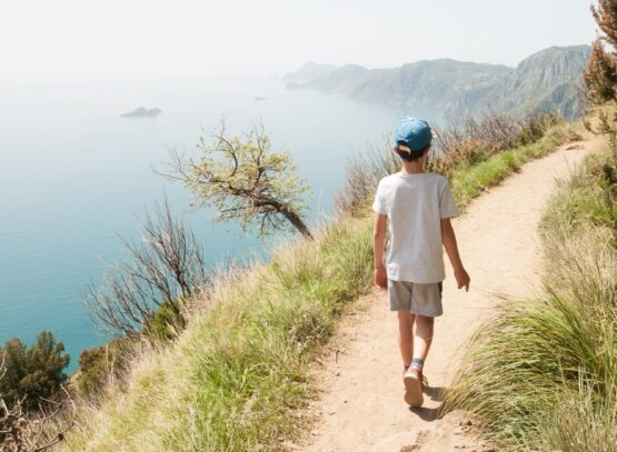 Positano, Italy - April 25, 2019: Child from behind walks on the path of the gods with panoramic sea