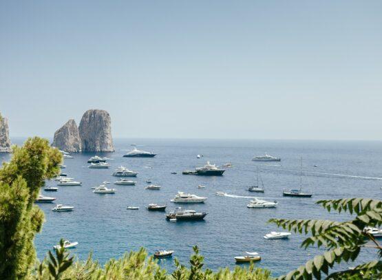 Boats sailing in Amalfi Coast against sky