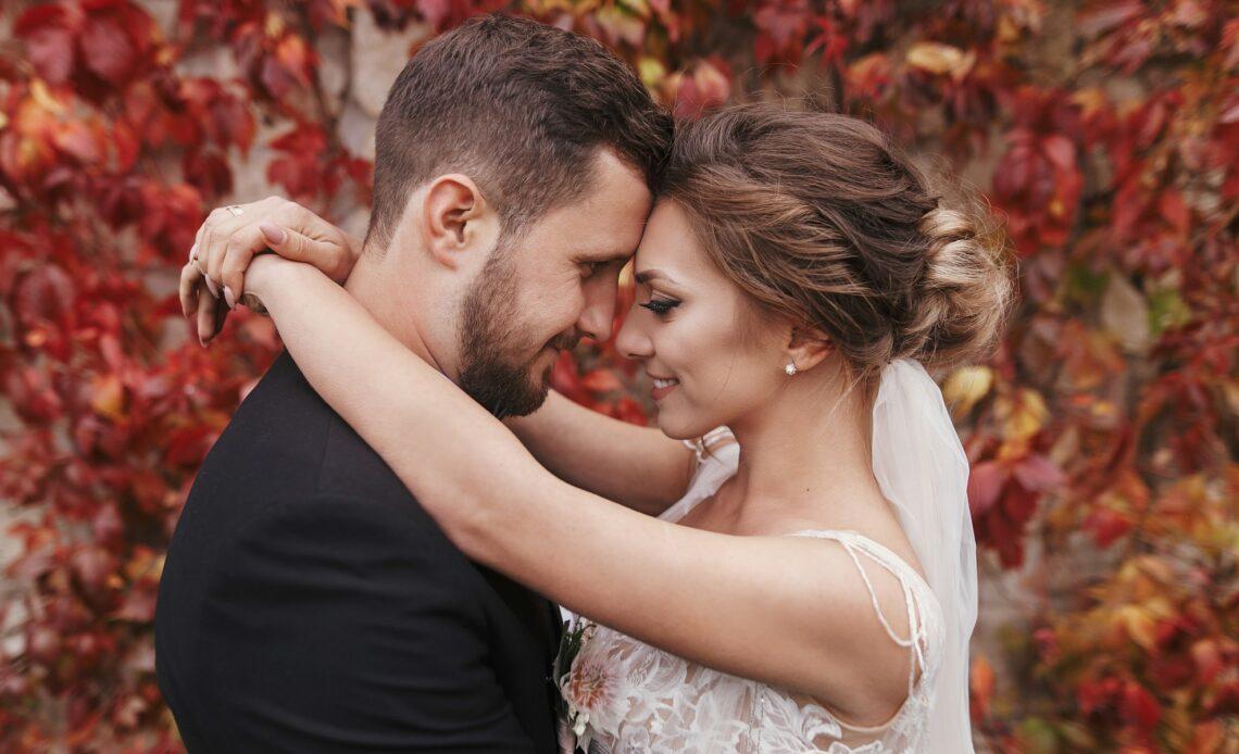 Matrimonio autunnale, sposo e sposa con fondo di foglie rosse