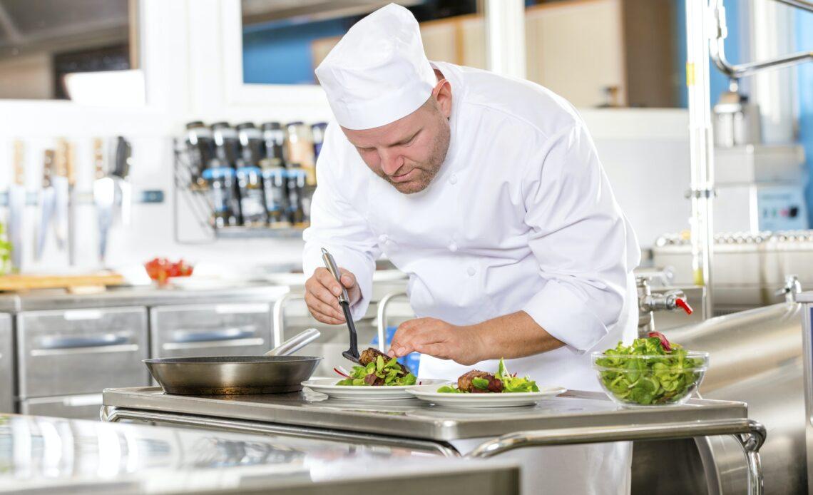Chef prepares steak dish at gourmet restaurant kitchen